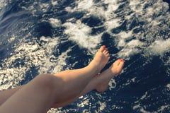 握她的在海上的妇女脚 免版税库存照片