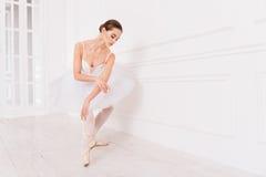 握她的在膝盖的嫩芭蕾舞女演员胳膊 免版税库存图片