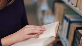握她的在页的手指读一本书的女孩在图书馆里 股票录像