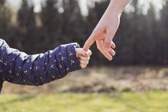 握她的女儿手的母亲 免版税库存图片