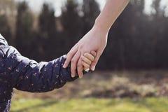 握她的女儿手的母亲 图库摄影