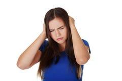 握她的耳朵的沮丧的少妇 免版税库存照片