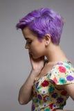 握她的面孔的紫罗兰色短发妇女 免版税库存图片