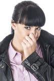 握她的鼻子的可爱的妇女停止难闻的气味或芳香 免版税图库摄影