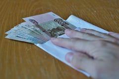 握它的在俄国货币俄罗斯卢布的男性手手指在木桌上 免版税库存图片