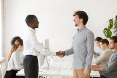握害羞的男性白种人求职者的手的黑人雇主 库存照片