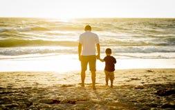 握小儿子的手的愉快的父亲一起走在与赤足的海滩 免版税图库摄影