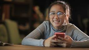 握巧妙的电话手中微笑的面孔的亚裔少年 股票视频