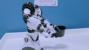 握帽子和移动的手的有人的特点的机器人在未来陈列