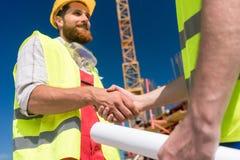 握建筑师的手的快乐的工作者在beginnin 免版税库存照片