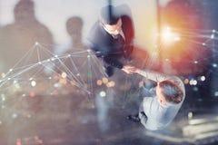 握手企业人在有网络作用的办公室 配合和合作的概念 两次曝光 图库摄影