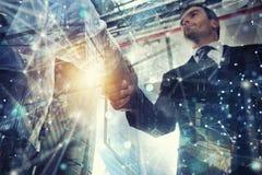 握手企业人在有网络作用的办公室 配合和合作的概念 r 免版税库存照片
