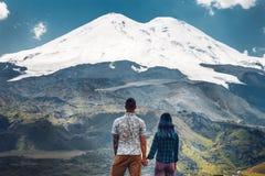 握手和享受厄尔布鲁士山的看法愉快的夫妇 免版税库存照片
