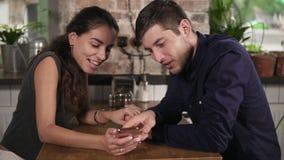 握手和使用电话的浪漫年轻夫妇为娱乐在咖啡店 也约会我浪漫看到相似的工作的画廊 股票视频