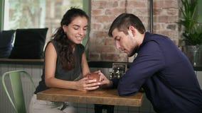 握手和使用电话的逗人喜爱的年轻夫妇为娱乐在咖啡店 也约会我浪漫看到相似的工作的画廊 股票视频