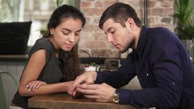 握手和使用电话的逗人喜爱的年轻夫妇坐在木桌上在咖啡店 也约会我浪漫看到相似的工作的画廊 股票视频