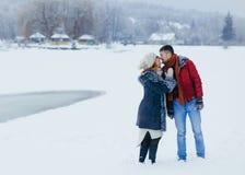 握手和几乎亲吻在多雪的乡下的可爱的年轻夫妇的水平的全长射击 库存照片