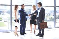 握手和微笑,当站立在办公室的两个确信的商人与小组同事一起时 库存图片