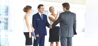 握手和微笑,当站立在办公室的两个确信的商人与小组同事一起时 免版税库存照片