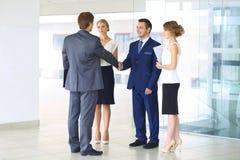 握手和微笑,当站立在办公室的两个确信的商人与小组同事一起时 库存照片