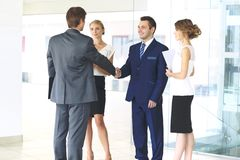 握手和微笑,当站立在办公室的两个确信的商人与小组同事一起时 免版税库存图片