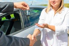 握手和汽车移交钥匙  免版税库存照片
