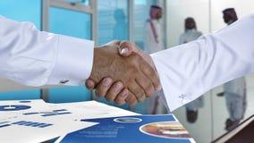 握手和签署协议或a的沙特阿拉伯商人 库存照片