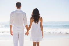 握手和观看海洋的有吸引力的夫妇 免版税图库摄影