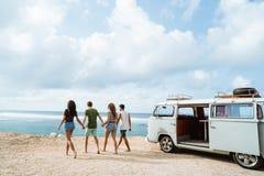 握手和走在海滩的朋友在一好日子 库存照片
