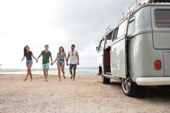 握手和走在海滩的朋友在一好日子 免版税图库摄影