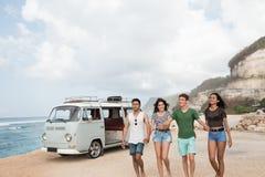 握手和走在海滩的朋友在一好日子 免版税库存照片