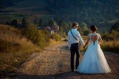 握手和走沿土气路的后面观点的新婚佳偶到山在日落期间 免版税库存照片