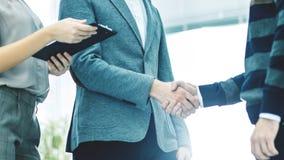 握手在关于合同的讨论的以后商务伙伴在一个明亮的办公室 免版税图库摄影
