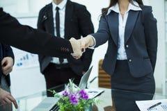 握手在关于合同的讨论的以后商务伙伴在工作地点 库存图片