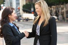 握手在办公室外的两名女实业家 免版税库存图片