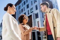 握手在城市街道上的愉快的人民 免版税库存照片