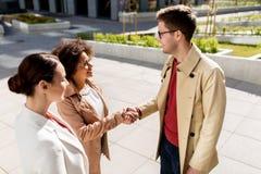 握手在城市街道上的愉快的人民 库存照片