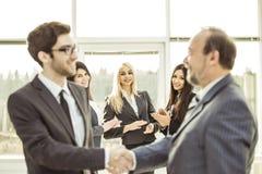 握手在开始企业交涉前的商务伙伴在背景鼓掌 库存图片