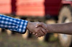 握手在拖拉机前面的农夫 免版税库存照片