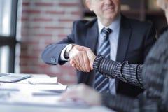 握手在桌面附近的商务伙伴在办公室 图库摄影