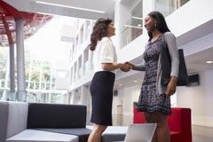 握手在现代办公室大厅的两名女实业家  免版税库存照片