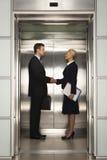 握手在电梯的企业同事 免版税库存照片