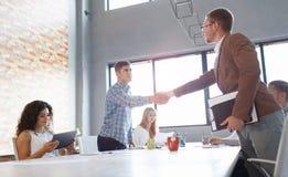 握手在轻的背景的办公室工作者 成功的业务会议 黑色通信概念收货人电话 库存照片