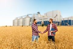 握手在麦田,农夫` s协议的人们 背景的谷物仓库终端 农业农艺师 库存照片