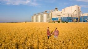 握手在麦田,农夫` s协议的人们 背景的谷物仓库终端 农业农艺师 免版税库存照片