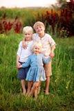 握手外面在t的三个珍贵的矮小的白肤金发的孩子 免版税库存照片