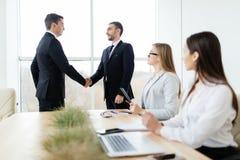握手得到的商人在会议室同意合同的标志 免版税库存照片