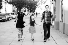 握手步行沿着向下街道的笑剧快乐的家庭 免版税库存照片