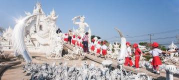 握手的一个小组基本的学童,当走到白色寺庙时 khun rong??wat 免版税库存图片