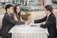 握手的三个商人在桌上 免版税库存图片